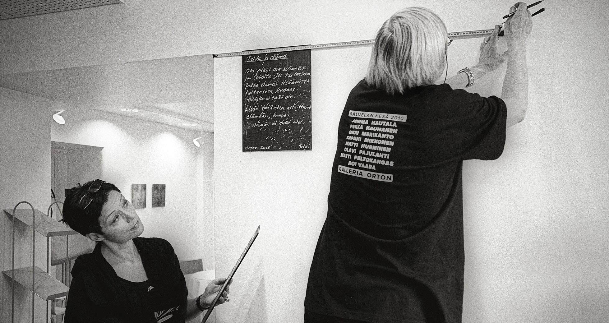Kesänäyttelyn ripustuskuva. Ripustamassa galleristi Sirpa Viljanen ja taidemaalari Olavi Pajulahti.