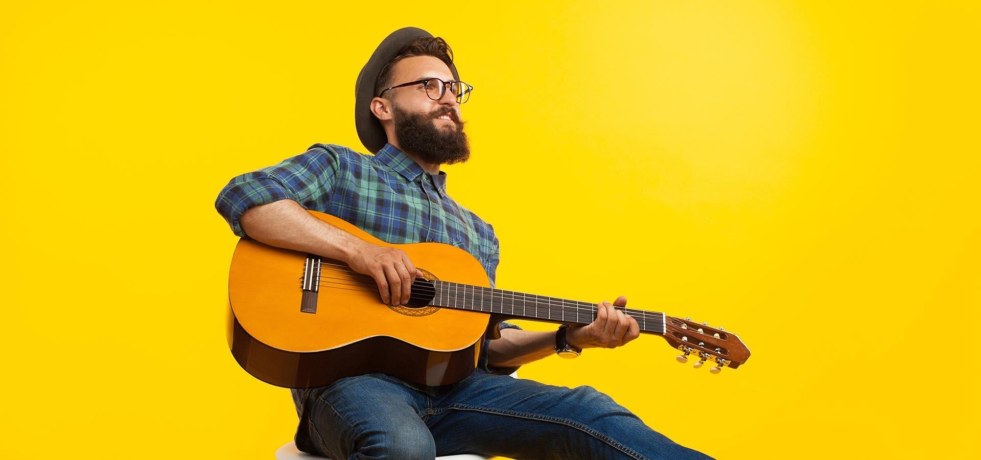 Nuorehko parrakas mies soittaa akustista kitaraa.