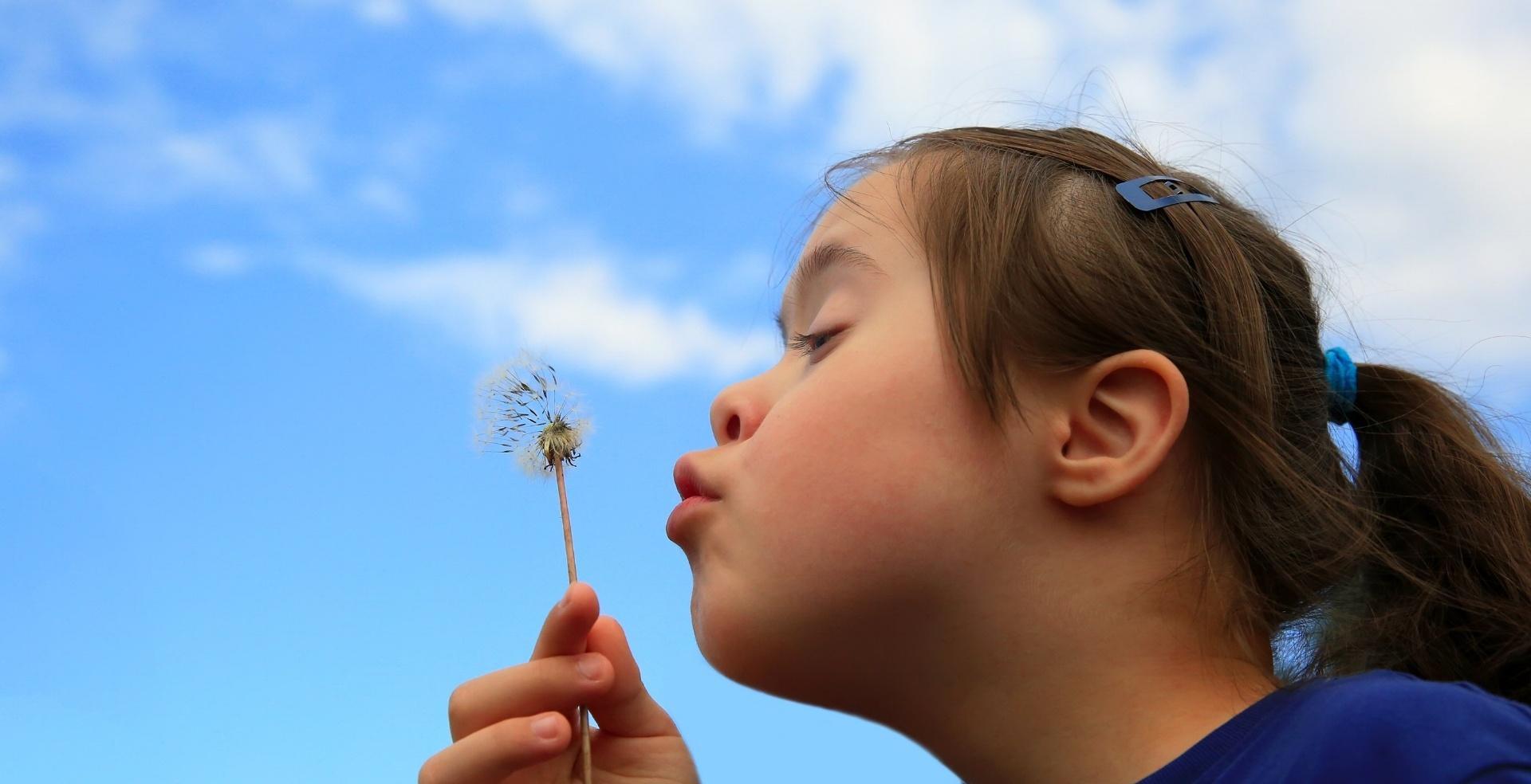 Taustalla kesäinen taivas ja tyttö puhaltelee voikukan haituvia.
